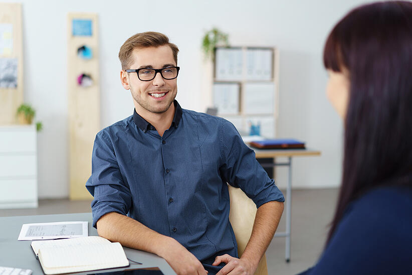 Handsome confident young businessman in glasses leaning back relaxing in his chair as he chats to a female colleague