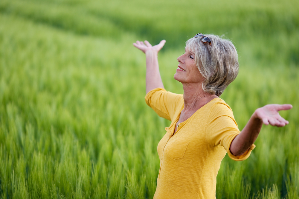 mature woman with outstretched arms in nature