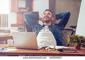 Satisfied man sitting at desk working