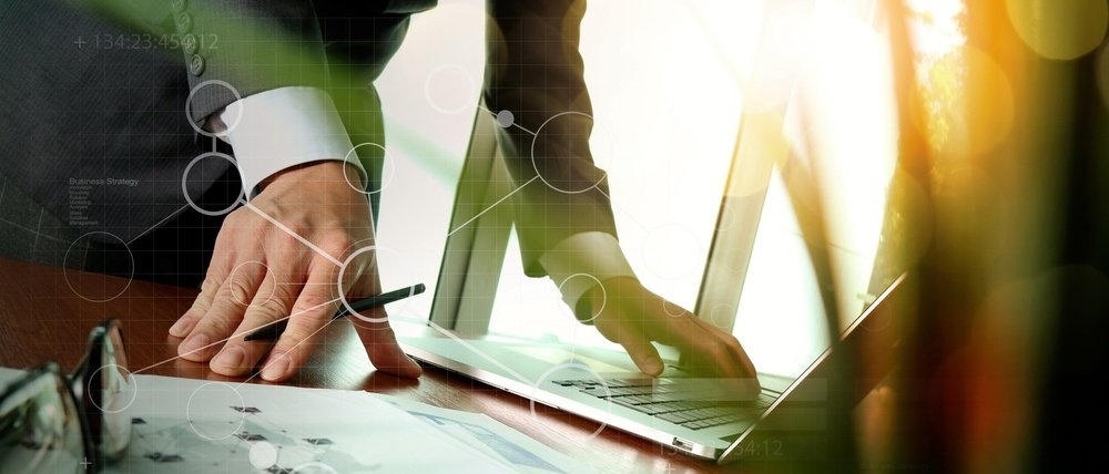 businessman hand working with new modern computer and business strategy documents digital layers with green plant foreground on wooden desk in office-278432-edited.jpeg