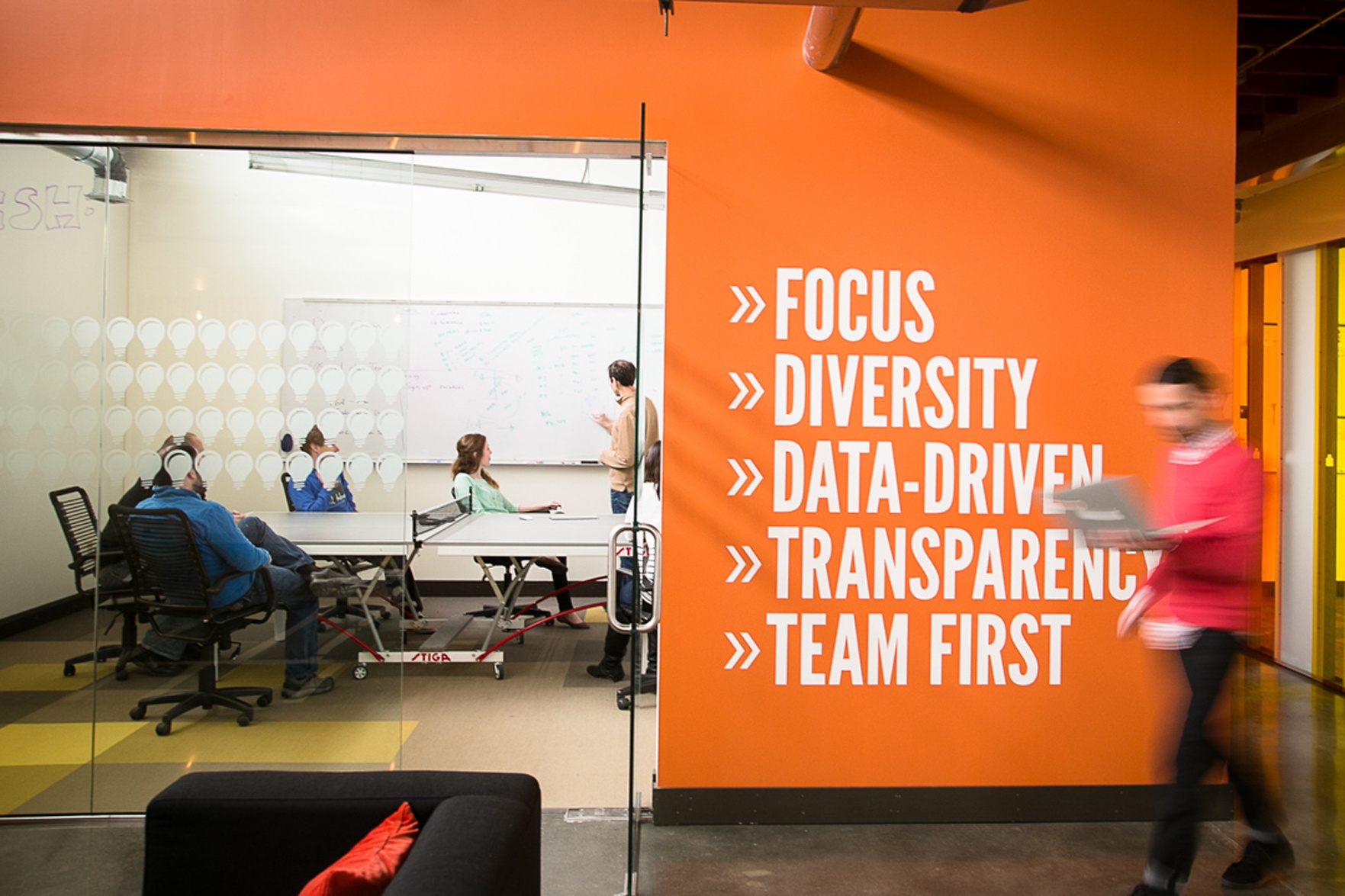 photo & video people working in an omaha startup office man walking with laptop  focus diversity data driven transparency team first