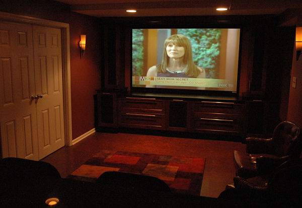 home theater with dimmed lights wall sconces custom cabinets and