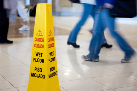 Floor with CAUTION: WET FLOOR sign to prevent slip and fall injuries