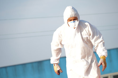 Man in hazmat suit removing asbestos from shipyard