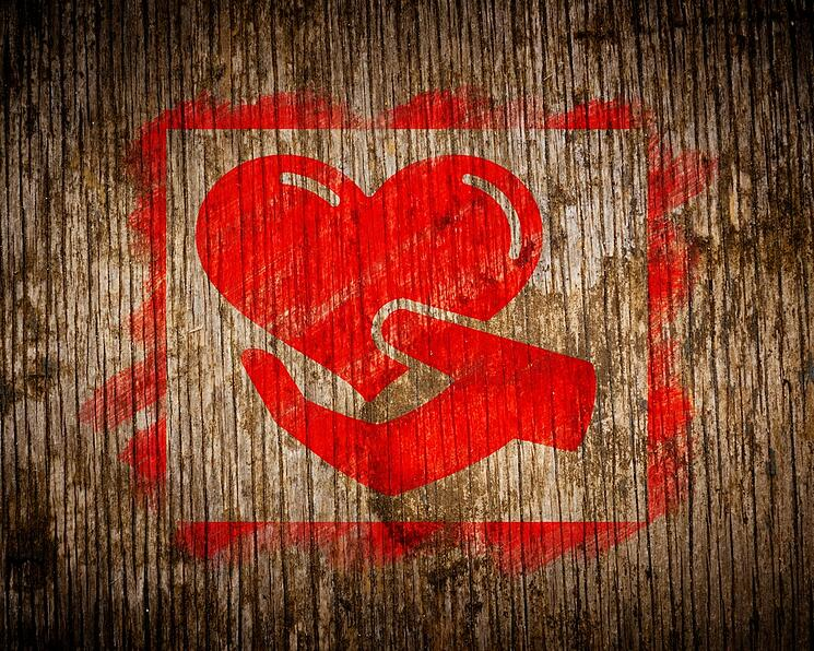 Charity. Red Icon of Heart in the Hand Painted by Stencil on Wood. Grunge Background.