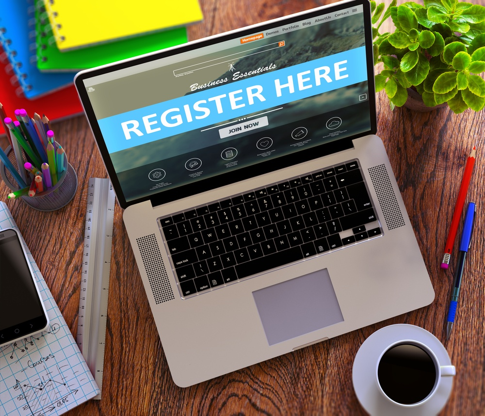 Register Here Concept. Modern Laptop and Different Office Supply on Wooden Desktop background.
