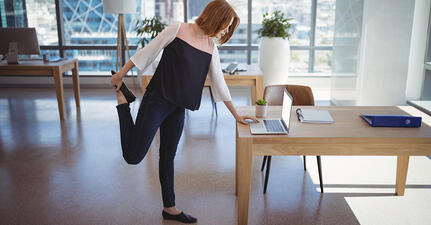 women in workplace at computer stretching