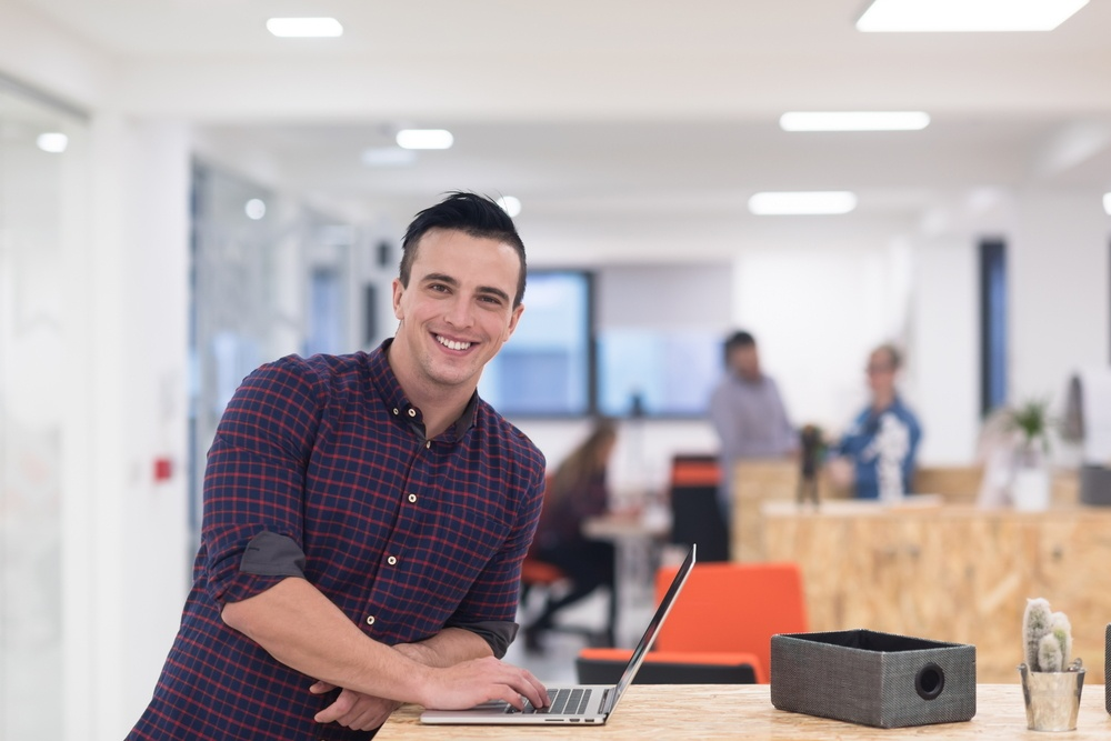 portrait of young businessman in casual clothes at modern  startup business office space,  working on laptop  computer