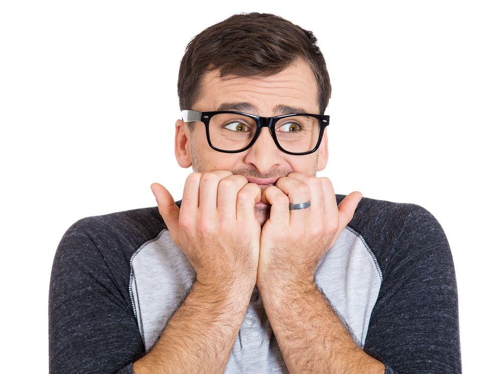 Closeup portrait of nervous, stressed young nerdy guy man with eyeglasses biting fingernails looking anxiously craving something isolated on white background. Negative emotion expression feeling-1