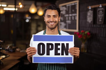 Smiling barista holding open sign in the bar