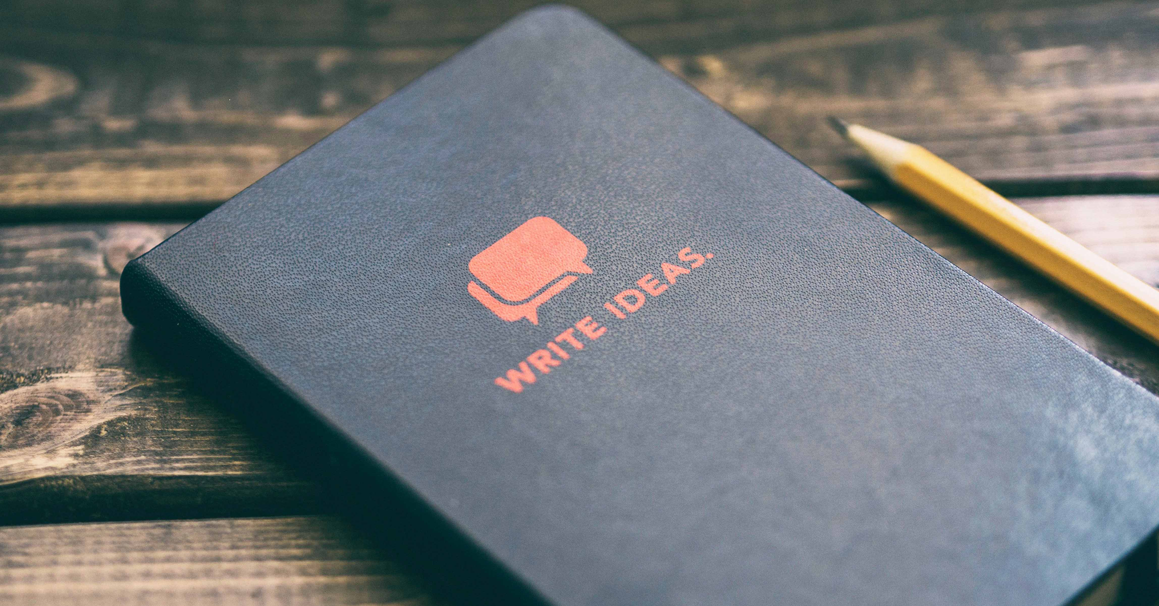 Photograph of a black, leather-bound journal with the words 'write ideas' on it. A pencil sits beside it.