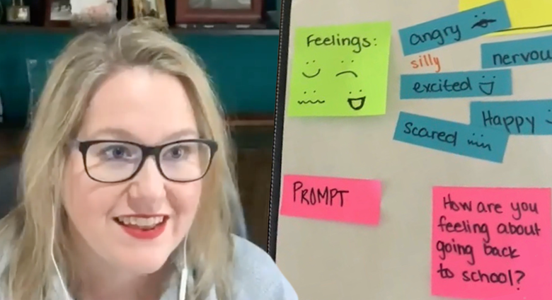 """An animated teacher with earbuds in looks at the camera. She has a poster board behind here with the text """"Prompt"""" next to the question """"How are you feeling about going back to school?"""" Additional text (""""angry,"""" """"nervous,"""" """"excited,"""" """"bored,"""" """"happy,"""" """"scared"""") with the heading of """"Feelings"""" is on the board as well."""