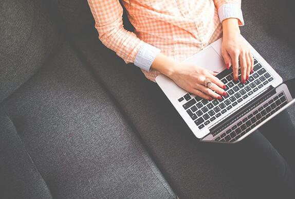 Woman sat on her laptop to represent boosting blog visibility