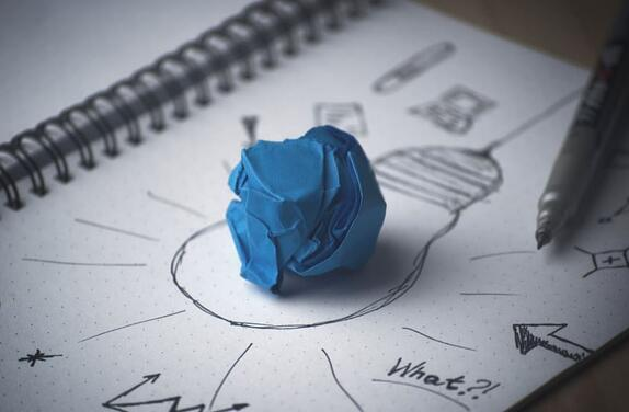 Ball of blue paper on top of a drawing of a lightbulb to represent buyer personas