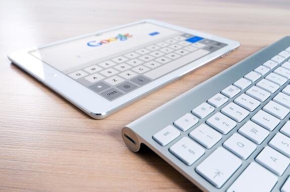 A tablet displaying the Google search page next to a keyboard to represent on-page SEO solutions