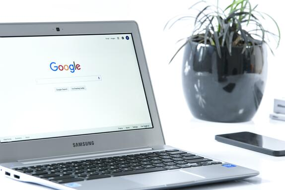 Open laptop displaying Google search page next to a phone and potted plant to represent Google medic update