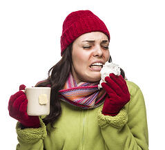 photodune-5866039-sick-woman-wearing-winter-clothing-blowing-her-sore-nose-and-holding-cup-of-hot-tea-on-white-xs