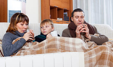 photodune-6957709-freezing-family-of-three-warming-near-warm-radiator-xs