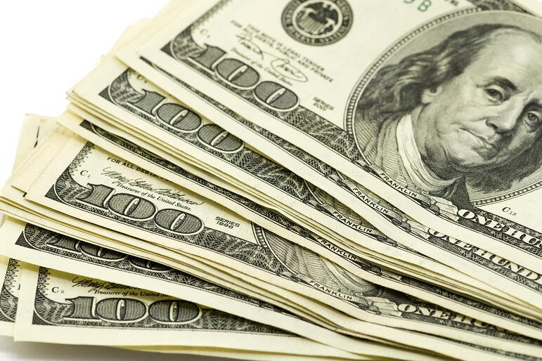 Banner Image: Handful of one hundred dollar bills to represent cashflow at a startup.