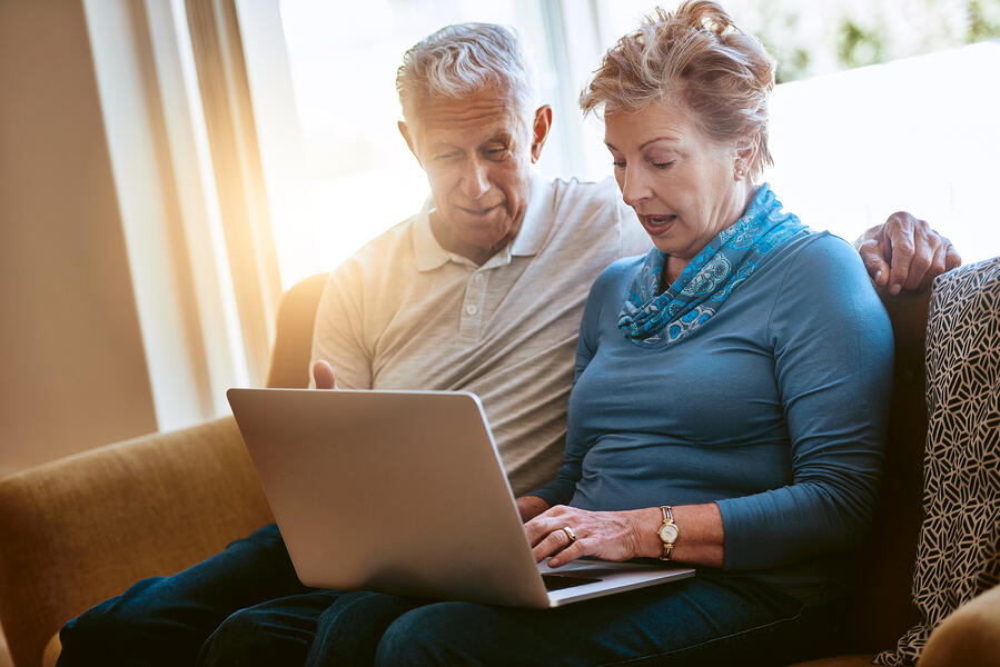 Older couple sitting in front of a laptop computer researching trustworthy financial advisor websites www.paladindigitalmarketing.com