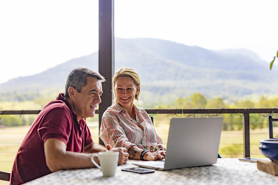 Older couple sitting at a table looking at financial advisor websites on their laptop