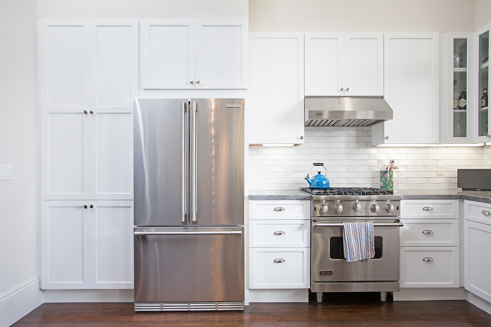 white fridge in kitchen. stainless steel appliances and white craftsman cabinets in our church street kitchen remodel. fridge w