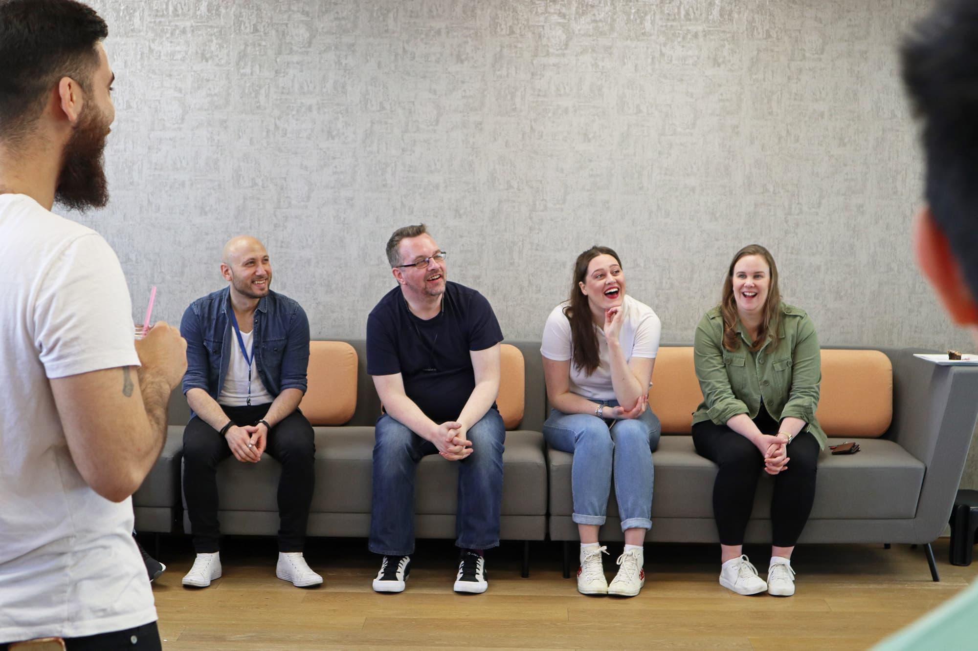 Sendible team members of a sofa, laughing