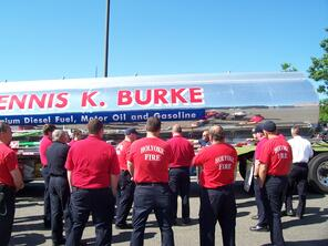 Group of fire fighters around a Dennis K. Burke truck recieving training