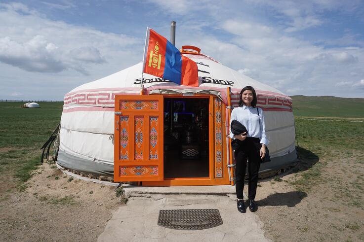 Image shows a woman standing in front of a ger with a Mongolian flag