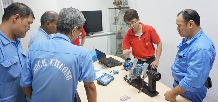 Image shows an SLS engineer explaining shaft alignment to employees of Hock Cheong Pte Ltd