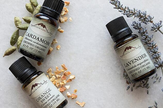 Lavender, orange, and cardamom essential oils laying on counter with their botanicals