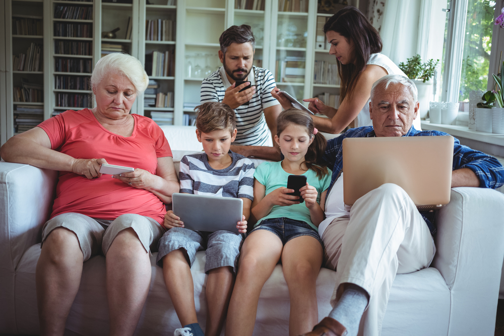 Multi-generation family sitting on sofa and using laptop, mobile phone and digital tablet