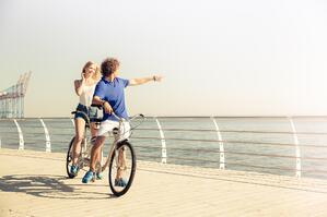 portrait-of-a-couple-riding-on-tandem-bicycle-outdoors-near-the-sea_BtpXJz0Bj