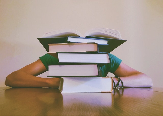 College Books Piled Over a Student's Head