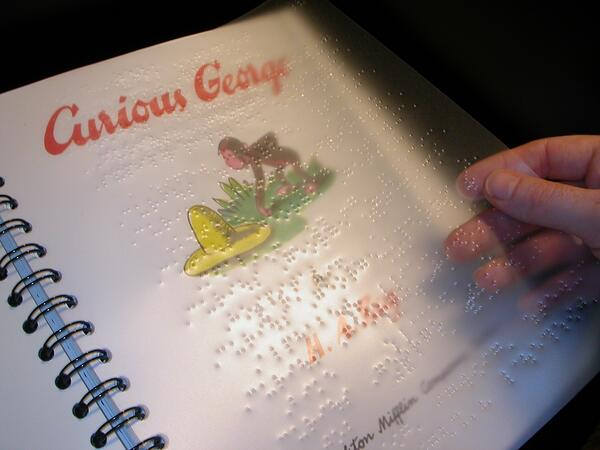 A copy of the original Curious George book with a plastic sheet of braille laid over its printed counterpart.