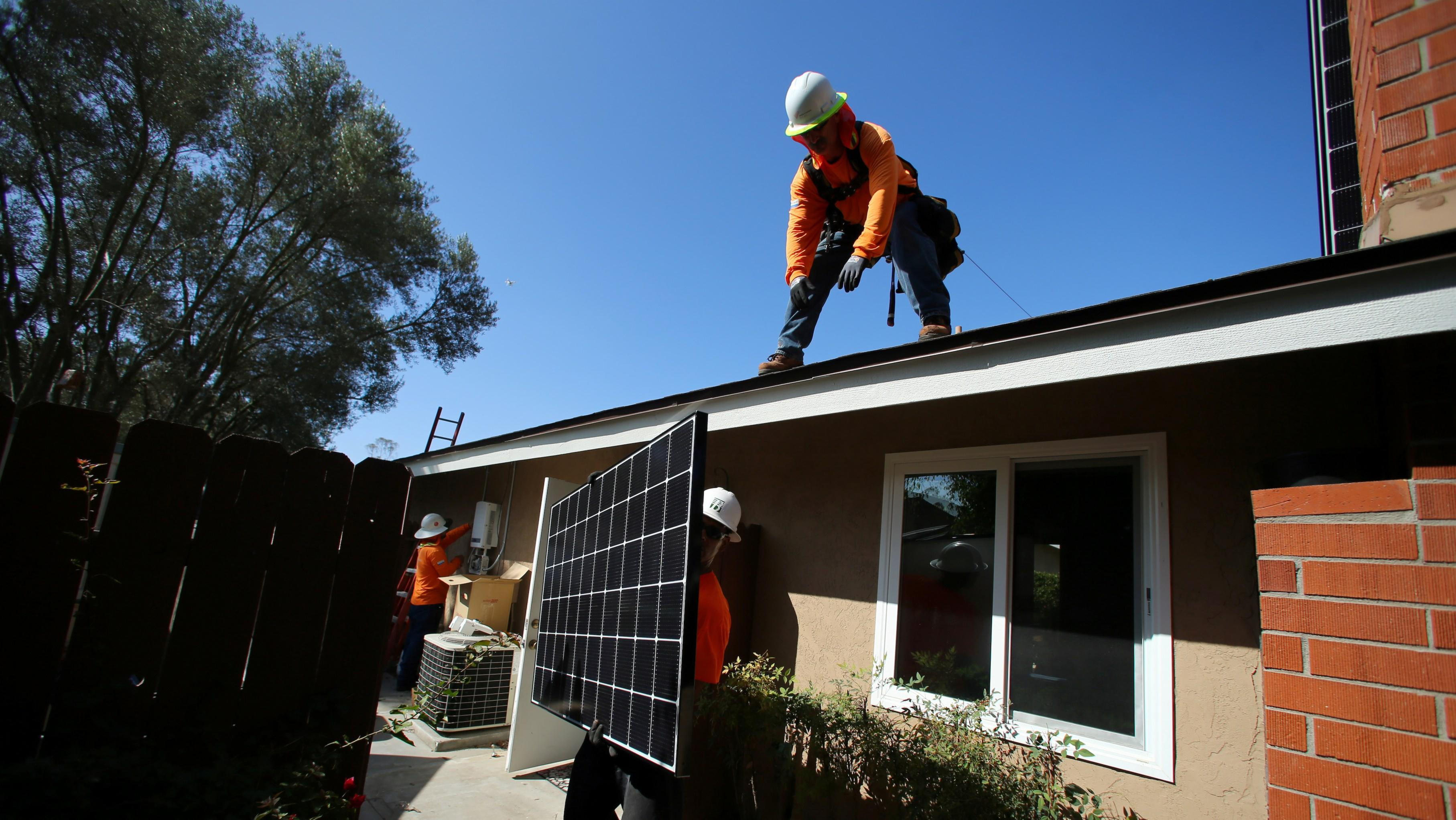 A worker hands a solar panel to another worker on top of a roof.
