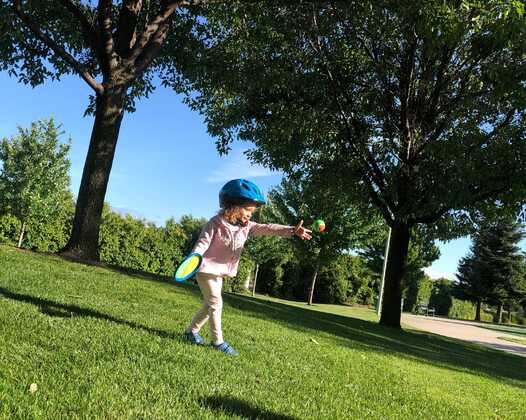 a child throwing a ball underhand