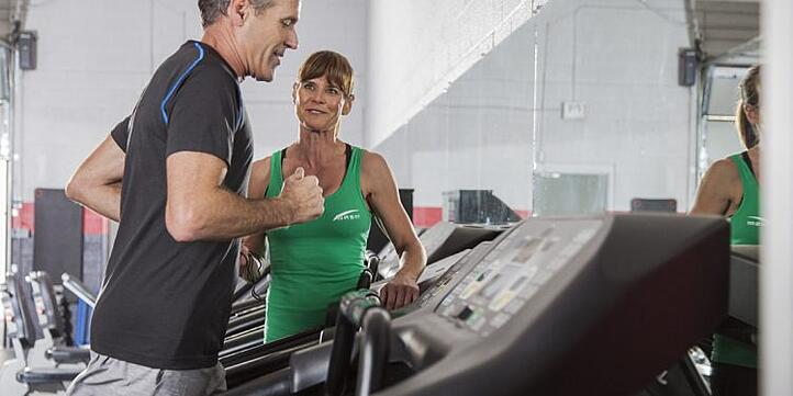 a personal trainer coaching a client on the treadmill