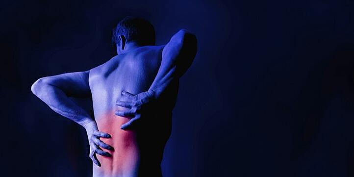 man clutching his lower back in pain