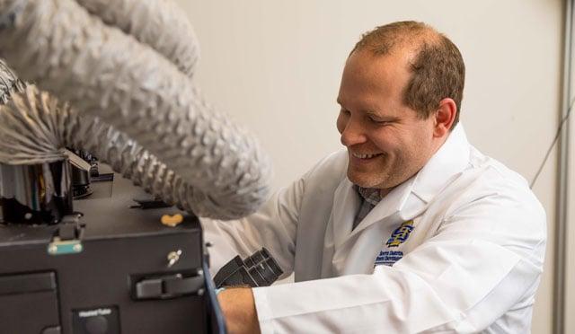 Butzin preparing to examine specimen with microscope