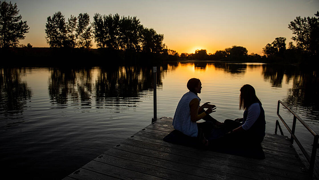 Couple on the dock at sunset on a lake in South Dakota