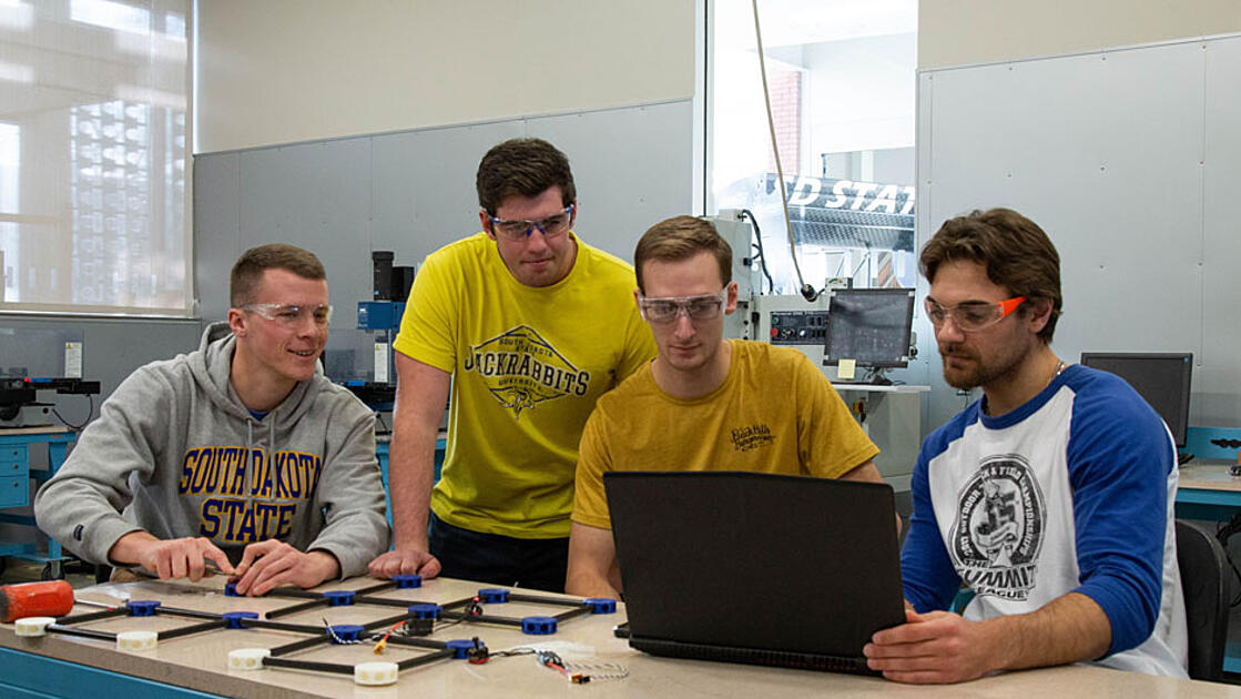 Four team members working on drone