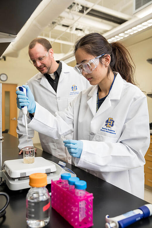 Reineke, left, and Guo pipetting