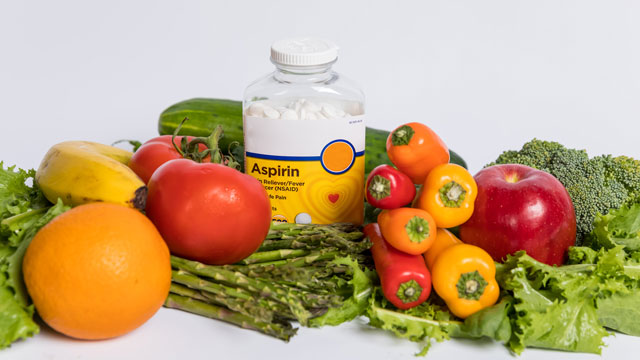 Aspirin bottle nestled among fruits and veggies