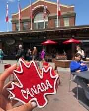 """A student is holding a red cookie shaped as a maple leaf with the word """"Canada"""" in the middle in front of a shopping center."""