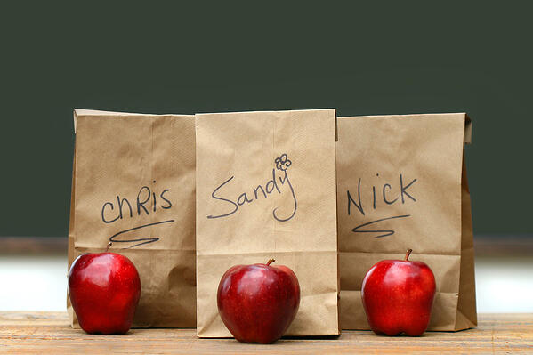 Apples and Lunch bags sit on a desk in honor of earth hour