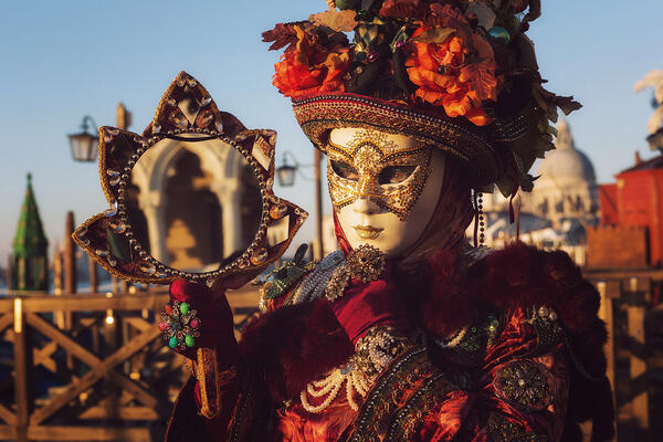 Person dressed up for Carnival with a venetian mask in Venice Italy