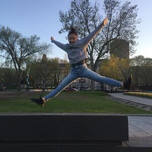 A student jumping with arms and legs in a star-formation in front of the parliament building in Ottawa.