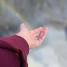 A student has a hand outstretched in front of a waterfall and a small rainbow that looks like it's landing in their hand.