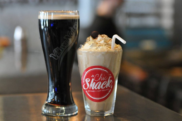 Two cups on a table and one is filled with coke and the other has a tall milkshake with whip cream from the Quebec City restaurant called Chic Shack.